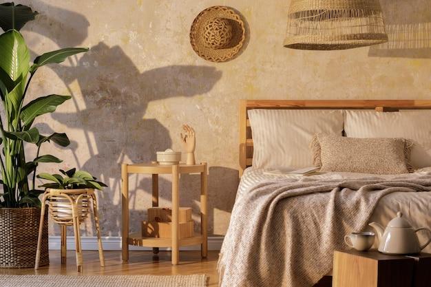 디자인 커피 테이블, 가구, 열대 식물, 등나무 장식 및 우아한 개인 액세서리를 갖춘 세련된 침실 인테리어. 아름다운 베이지 침대 시트, 담요 및 베개. 주형.