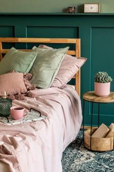 Стильный интерьер спальни с дизайнерским журнальным столиком, растением, книгой, полкой и элегантными личными аксессуарами. красивые простыни, одеяло и подушки. . современная домашняя постановка. обшивка стен.