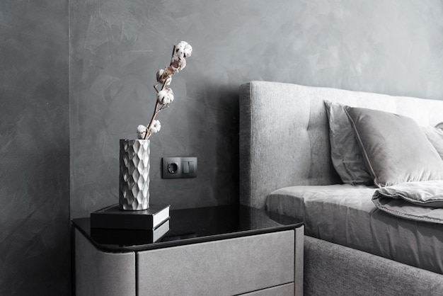 Stylish bedside table with dark book and vase with dried cotton branch on it