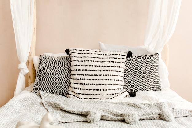 Стильная спальня бежевого цвета с кроватью с постельным бельем, подушками в стиле бохо