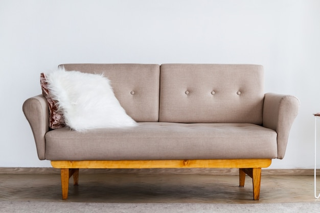A stylish beige sofa with a white fluffy pillow