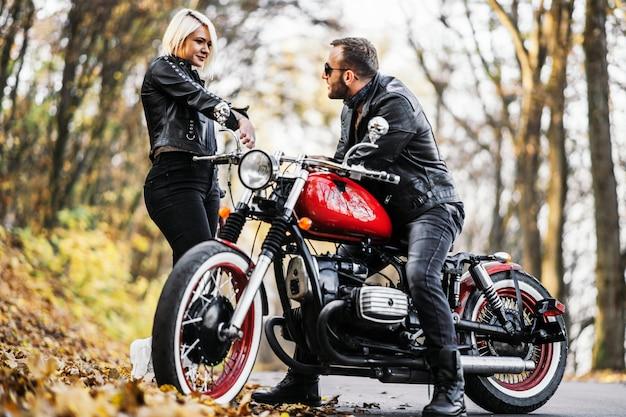 赤いバイクとスタイリッシュな自転車に乗るカップル