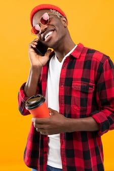 市松模様の赤いシャツで美しい笑顔でスタイリッシュな黒人アメリカ人が彼の手で黄色のスタジオの背景にコーヒーのガラスを保持しています。