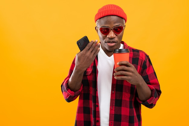 市松模様の赤いシャツで美しい笑顔を持つスタイリッシュな黒人アメリカ人が黄色のスタジオで彼の手でコーヒーを保持しています。