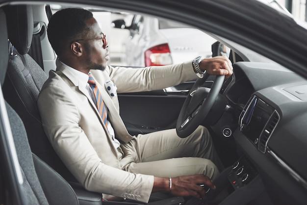 新しい高級車のホイールの後ろに座っているスタイリッシュな黒のビジネスマン。豊かなアフリカ系アメリカ人