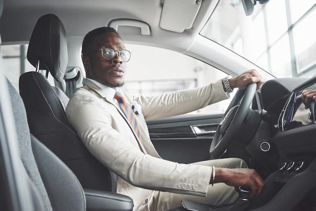 新しい高級車のホイールの後ろに座っているスタイリッシュな黒のビジネスマン。豊かなアフリカ系アメリカ人。