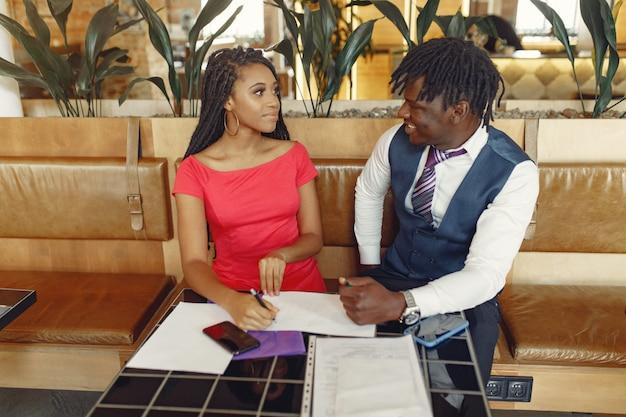 Стильная черная пара сидит в кафе и ведет деловую беседу