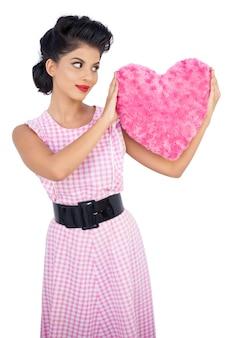 핑크 하트 모양의 베개를 들고 세련된 검은 머리 모델