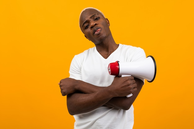 Stylish black handsome american man in white t-shirt holding a megaphone on isolated orange background