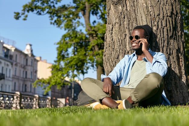 スタイリッシュな黒のヒップスターの男性がサングラス、帽子、ズボンとシャツを着て、大きな木の近くの緑の芝生で組んだ足に座って、スマートフォンで会話し、美しい天気と自然を楽しんでいます