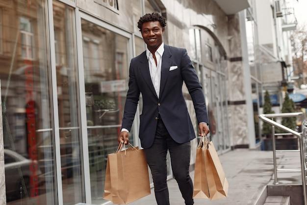 Стильный черный человек в городе с сумками