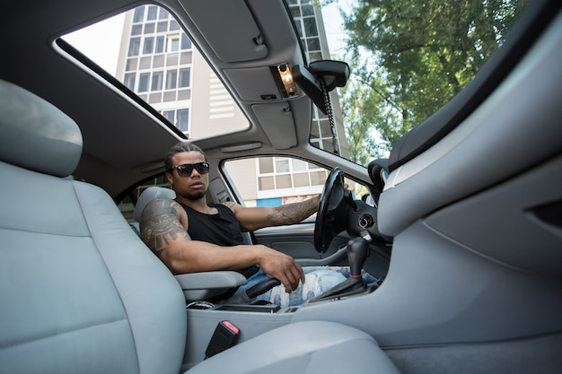高級車のハンドルの後ろに座っているスタイリッシュな黒人男性