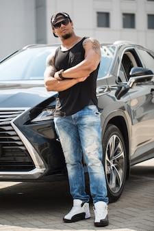 スタイリッシュな黒人男性が彼の豪華な車の横に立っています。