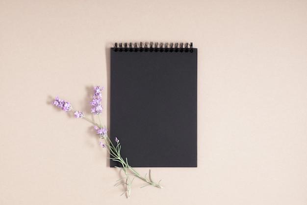 Стильный черный спиральный блокнот и цветок на бежевом фоне, плоский вид сверху
