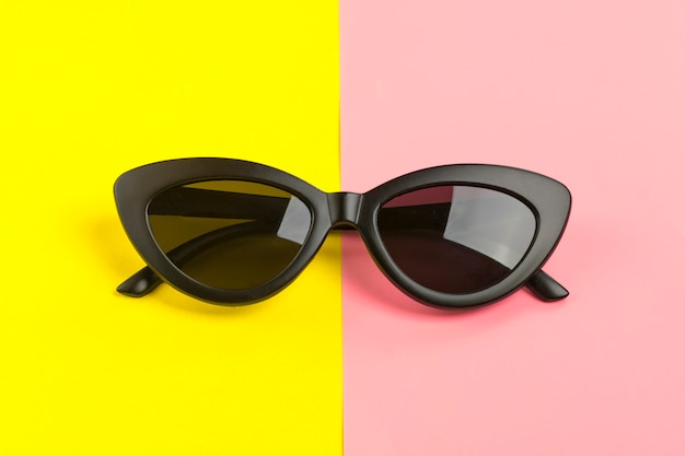 Stylish black sunglasses isolated on trendy pink flat lay