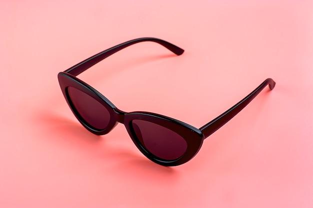 Stylish black sunglasses isolated on trendy pink