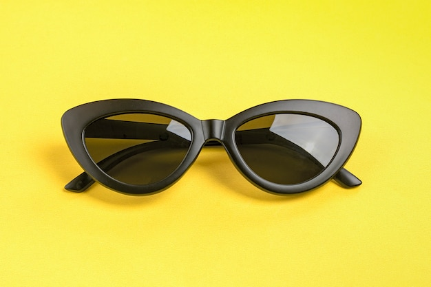 Stylish black sunglasses isolated on yellow