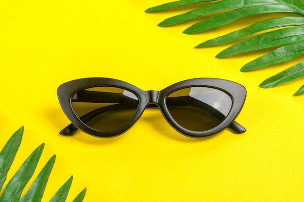 Stylish black sunglasses and palm leaves on trendy yellow