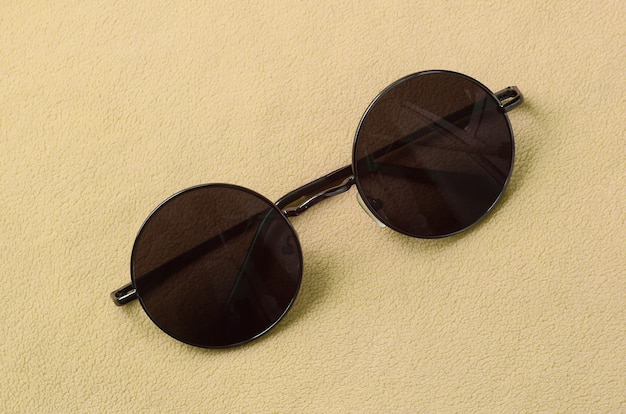 Stylish black sunglasses with round glasses lies on a blanket