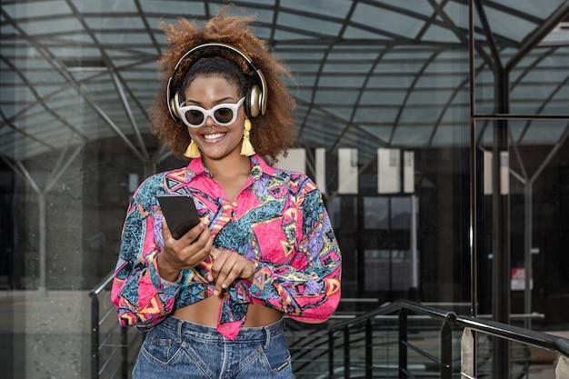 Стильная черная женщина со смартфоном, наслаждаясь музыкой в гарнитуре