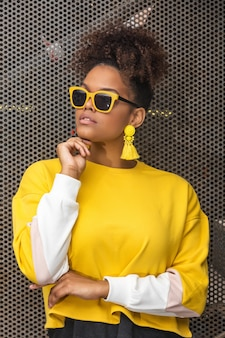 Stylish black woman in yellow outfit
