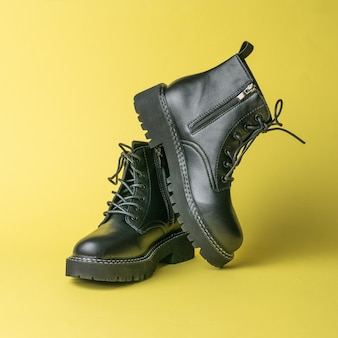 Stylish black youth leather boots on a yellow surface