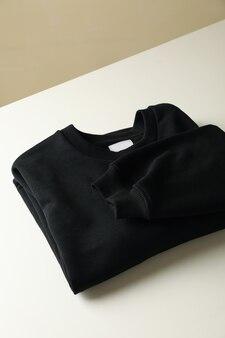 Стильная пустая черная толстовка на белом столе