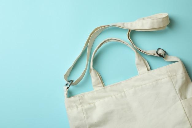 Stylish blank eco bag on blue background