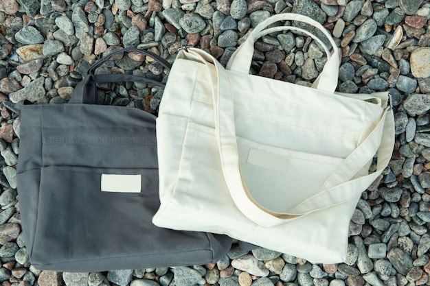 Stylish blank eco bags outdoor on pebbles