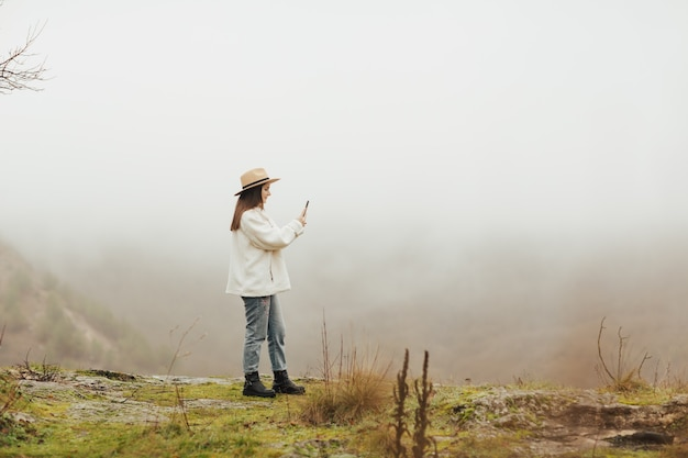 Stylish blogger on a hill photographing a rocky destination, pine forest and foggy hills.