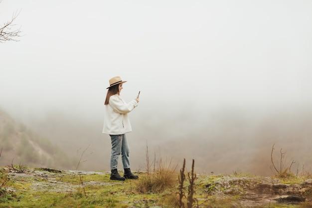 바위가 많은 곳, 소나무 숲, 안개가 자욱한 언덕을 촬영하는 언덕 위의 세련된 블로거.