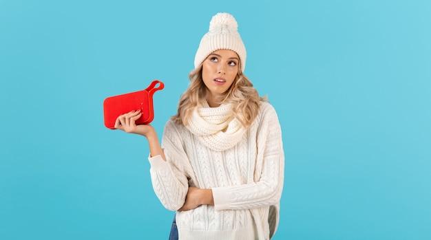Стильная блондинка красивая молодая женщина, держащая беспроводной динамик, слушает музыку в белом свитере и вязаной шляпе, позирует на синем