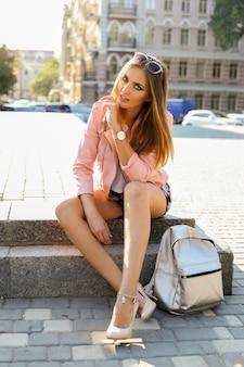 屋外でポーズをとるピンクの革のジャケットのスタイリッシュな金髪のヨーロッパの女性。