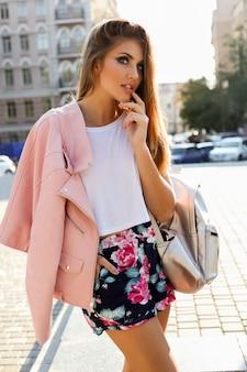 Elegante donna europea bionda in giacca di pelle rosa in posa all'aperto.
