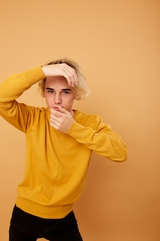 Stylish blond guy dressed in yellow sweater and black jeans is posing on the beige background in the studio .
