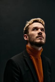 暗い背景のオレンジ色のセータージャケットモデルのクローズアップでファッショナブルな服を着たスタイリッシュな金髪の男