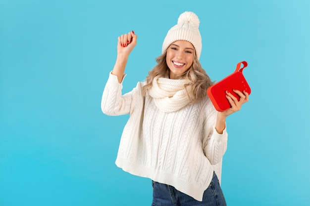 Stylish blond smiling beautiful young woman holding wireless speaker listening to music happy dancing wearing white sweater and knitted hat winter style fashion posing