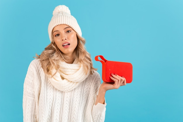 Stylish blond smiling beautiful young woman holding wireless speaker listening to music happy wearing white sweater and knitted hat posing on blue