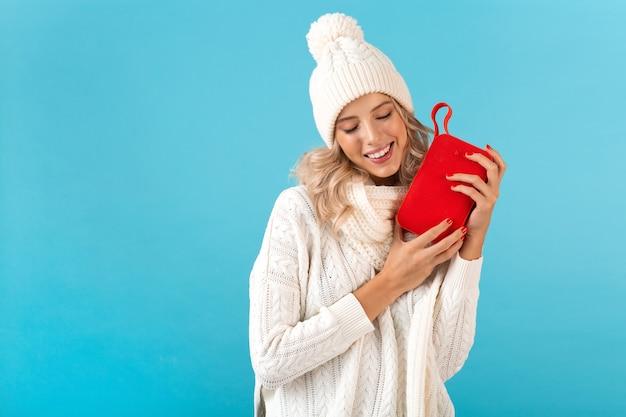 Elegante bionda sorridente bella giovane donna che tiene altoparlante wireless ascoltando musica felice indossando maglione bianco e cappello lavorato a maglia in stile invernale moda posa