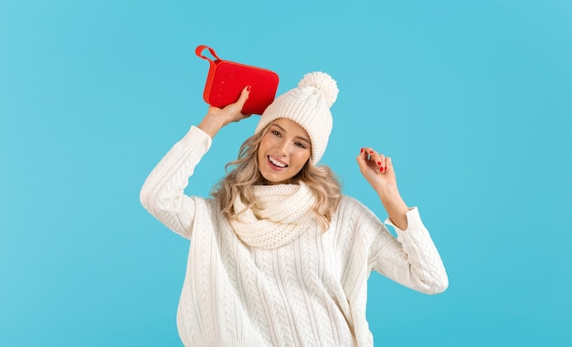 Stylish blond smiling beautiful young woman holding wireless speaker listening to music wearing white sweater and knitted hat posing on blue