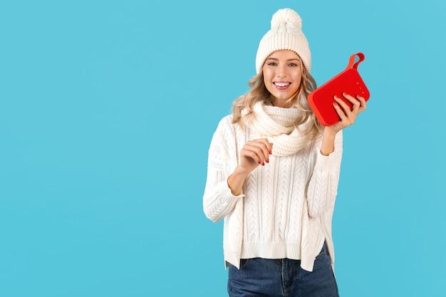 Стильная блондинка улыбается красивая молодая женщина, держащая беспроводной динамик, слушая музыку, счастливые танцы в белом свитере и вязаной шапке, зимняя мода, позирует, изолированные на синей стене