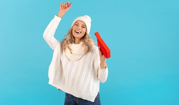 흰색 스웨터와 니트 모자 겨울 스타일 패션 포즈를 입고 음악 행복 춤을 듣고 무선 스피커를 들고 세련된 금발 웃는 아름다운 젊은 여자