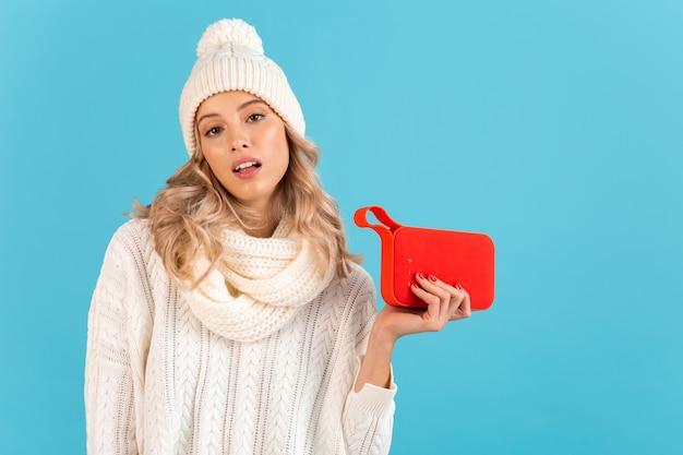 Стильная блондинка улыбается красивая молодая женщина, держащая беспроводной динамик, слушает музыку, счастлива носить белый свитер и вязаную шляпу, позирует на синем