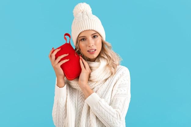白いセーターと青い背景で隔離の冬のスタイルのファッションポーズを身に着けて幸せな音楽を聴いてワイヤレススピーカーを保持しているスタイリッシュな金髪の笑顔の美しい若い女性