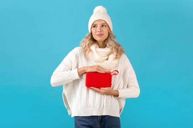 Стильная белокурая улыбающаяся красивая молодая женщина, держащая беспроводной динамик, слушает музыку, счастливая в белом свитере и вязаной шапке, позирует в зимнем стиле, изолирована на синей стене