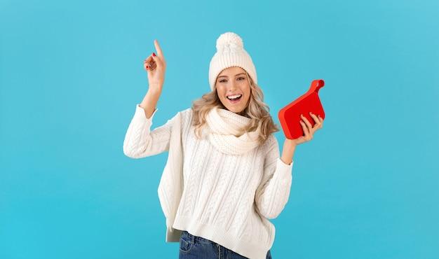 Стильная блондинка улыбается красивая молодая женщина, держащая беспроводной динамик, слушает музыку в белом свитере и вязаной шляпе, позирует на синем
