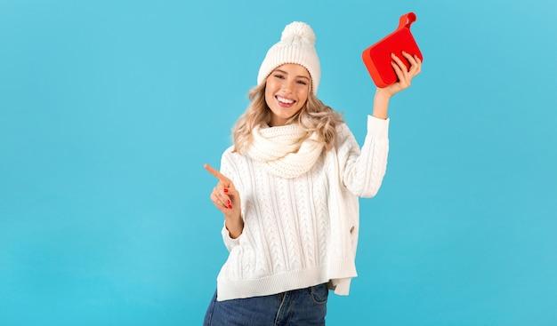 파란색에 흰색 스웨터와 니트 모자를 쓰고 음악을 듣고 무선 스피커를 들고 세련된 금발 웃는 아름다운 젊은 여자