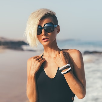 Stylish blond walking on the beach