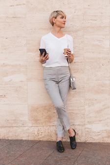 夏に屋外のベージュの壁に立ち、持ち帰り用のコーヒーとコピースペースを脇に見ながら、スマートフォンを保持している白いtシャツを着ているスタイリッシュなブロンドの女性