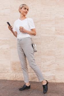 夏に屋外のベージュの壁に立ち、持ち帰り用のコーヒーとコピースペースを脇に見ながら、携帯電話を使用して白いtシャツを着ているスタイリッシュなブロンドの女性